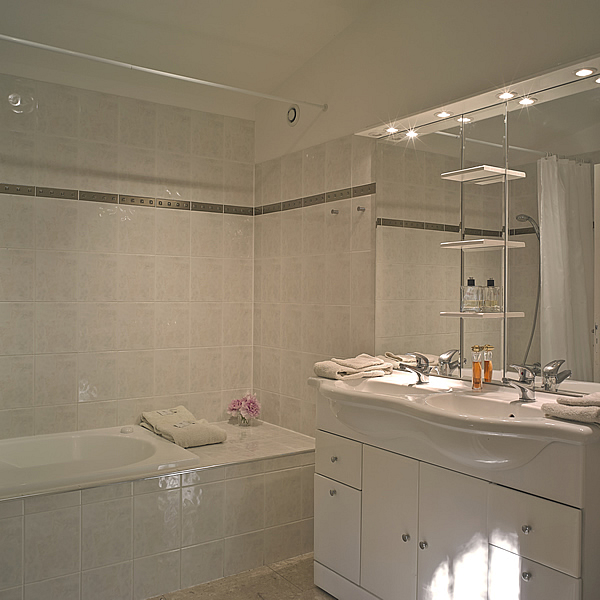Pomerol's spacious bathroom with a jacuzzi bath, two washbasins and a WC