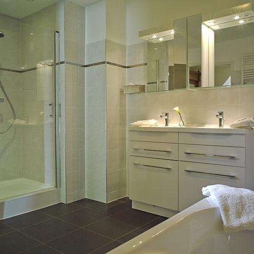 La deuxième salle de bains avec d'une baignoire avec jacuzzi, douche séparée et deux lavabos